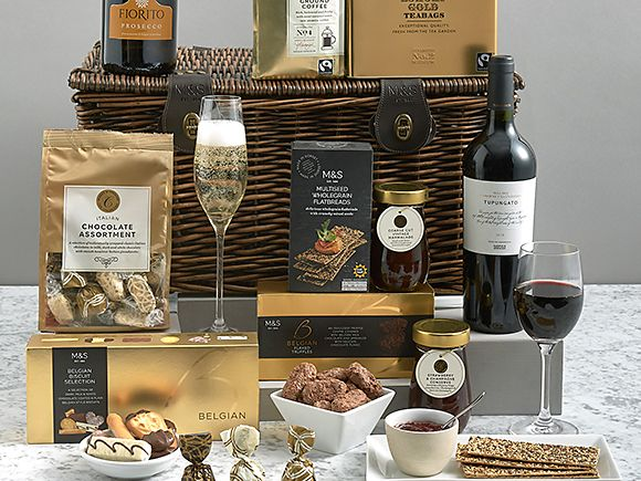 Luxury hamper surrounded by edible treats and drinks