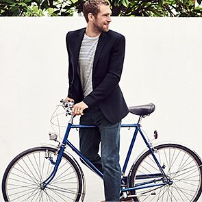 Man wearing jeans and blazer with bicycle