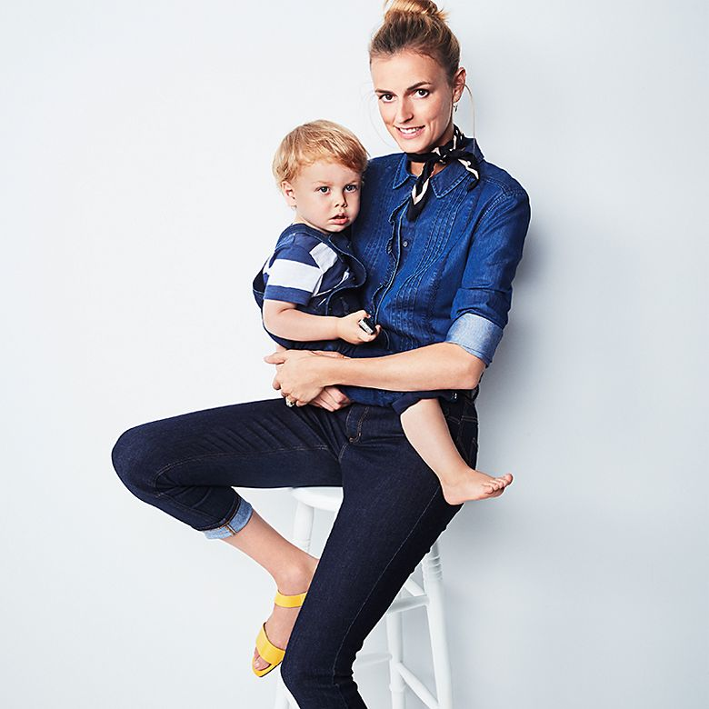 Model Jacquetta Wheeler wears denim shirt, neckerchief, jeans and holds toddler in dungarees