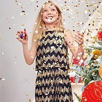 Girl wearing M&S party dress holding a sparkler