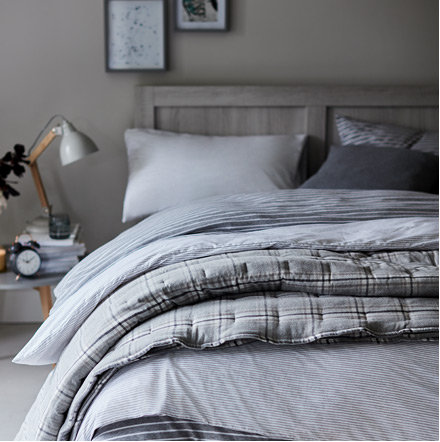 Grey Patterned Bed Linen On A Grey Wooden Bed