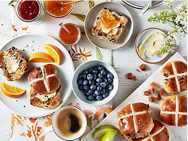 Hot cross buns with butter, a selection of jams and sliced fruit, and two cups of coffee