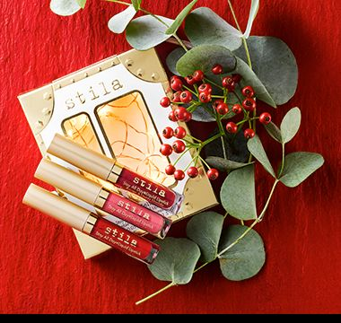 Stila Lipstick Set make-up gift surrounded by red berries and Christmas foliage