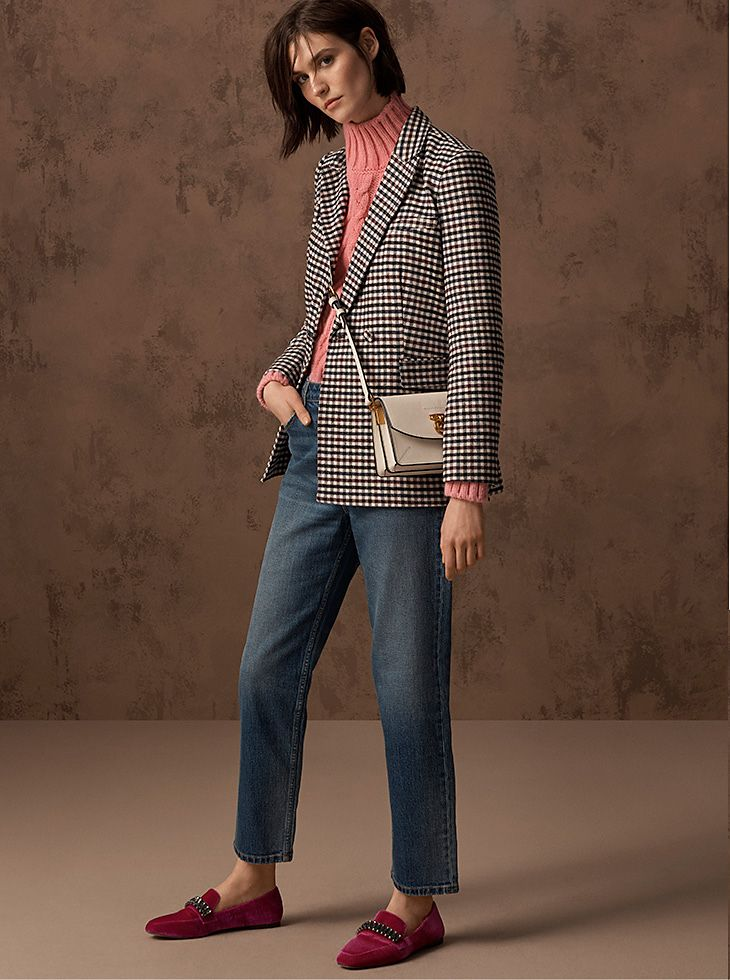 Model wears a black and white checked blazer over a pink cable-knit sweater and blue jeans with a white cross-body bag  and red loafers