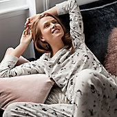 Woman lying on a sofa wearing grey llama-print pyjamas