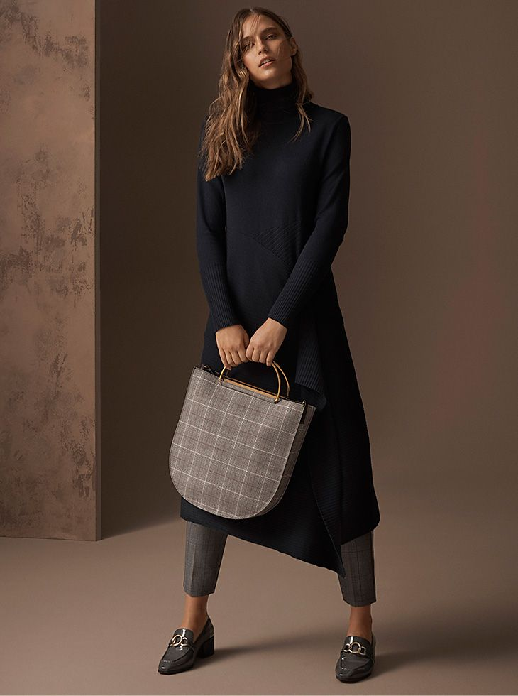 Model wears a navy jumper dress with an asymmetric hem over grey checked trousers with a grey checked top-handle bag and grey loafers