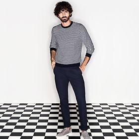 Man wearing a black and white cotton jumper, black trousers and trainers