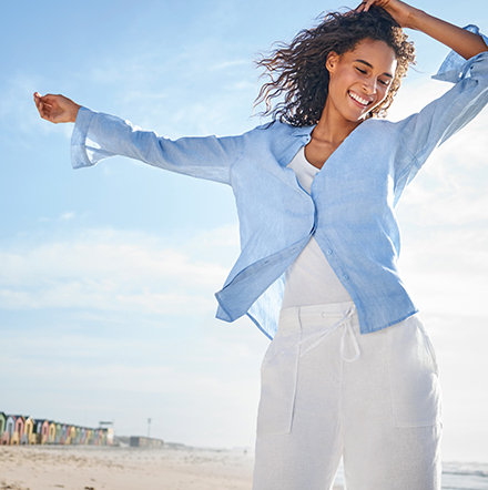 Woman by the sea wearing a blue linen shirt, white vest and white linen trousers
