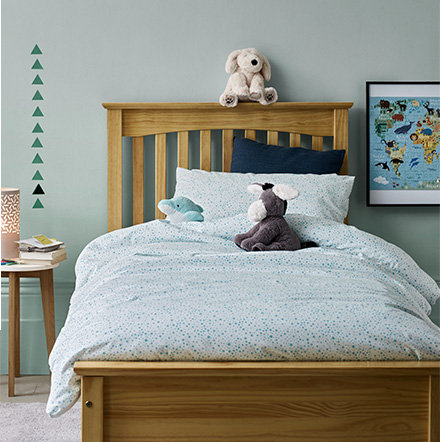 Children's bedding in a kids' bedroom with wooden bed