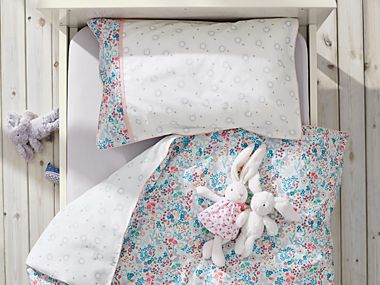 Children's single bed with floral duvet and toy bunny rabbit