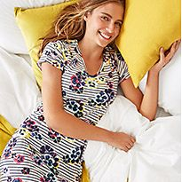 Woman on a bed wearing a printed short-sleeve nightdress