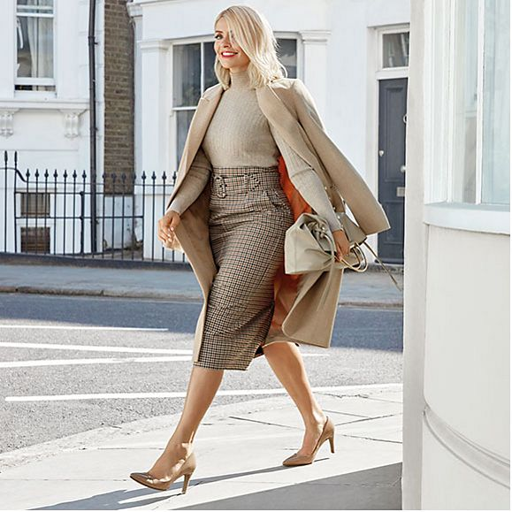 Holly Willoughby wearing a camel coat, ribbed roll-neck jumper, checked pencil skirt, nude pointed court shoes and an almond tote bag
