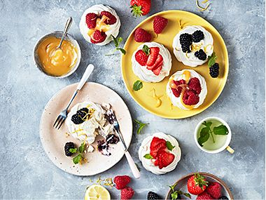 Plates of fruit-topped meringues and fresh berries