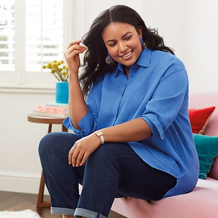Model wearing a blue linen shirt and indigo straight-leg jeans from the Curve collection