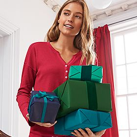 Woman carrying Christmas gifts wears red pyjamas