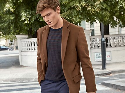 Oliver Cheshire wearing Must-Have chinos and a fitted brown coat