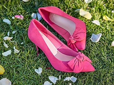 Pair of pink bow court shoes on grass