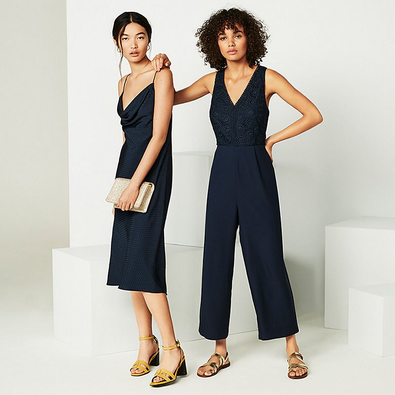 Two women wearing navy slip dress and navy jumpsuit