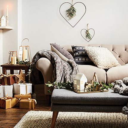 Sofa in living room with cushions, throws and Christmas decorations