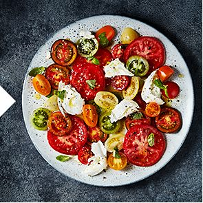 A plate of sliced tomatoes with buffalo mozzarella, basil and olive oil