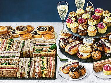 Selection of sandwiches, tarts and cakes with glasses of prosecco