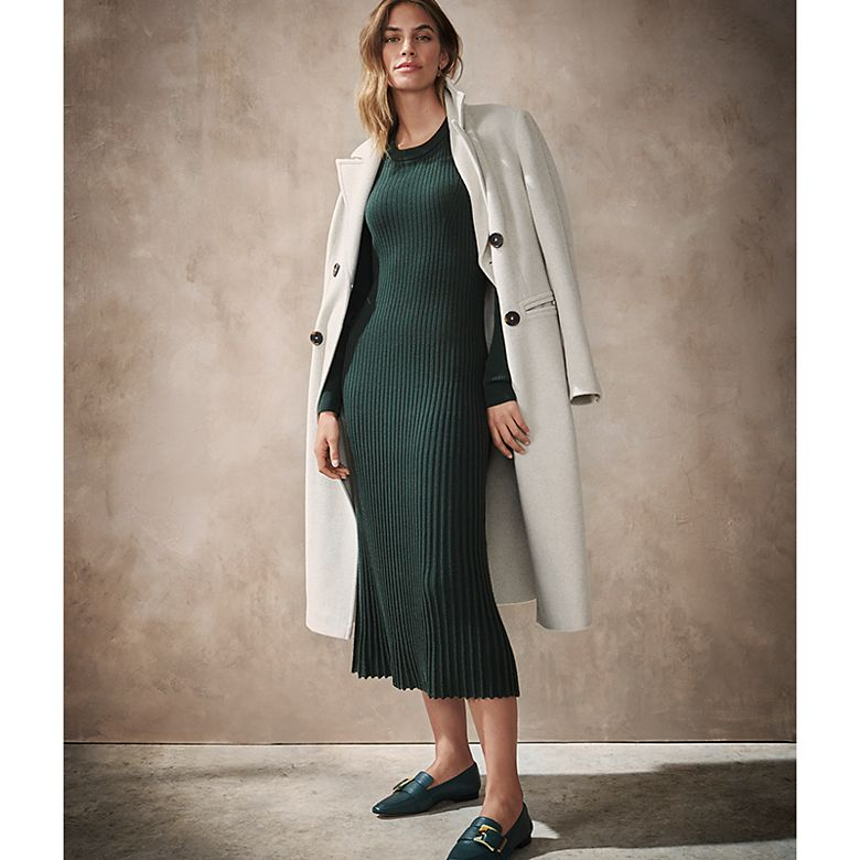 Woman wearing forest-green knitted jumper dress with white overcoat