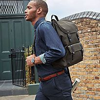 Man walking down a street with an M&S backpack
