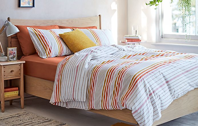 Patterned bedding on a wooden double bed