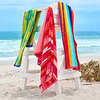 Bright colourful towels draped over a lifeguard chair on the beach