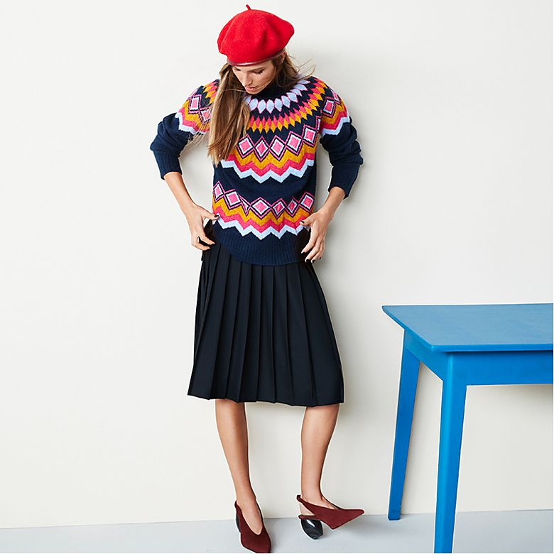 Model wears patterned jumper and pleated skirt