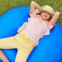 Girl lying in the sun wearing a straw hat, pink top and yellow denim shorts