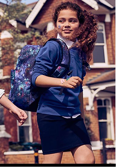 Girl wearing M&S school uniform with a school backpack