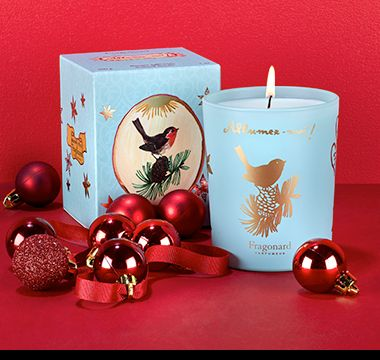 Fragonard Pine Tree Candle nestled among red baubles