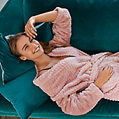 Woman lying on a green velvet sofa wearing a fluffy pink dressing gown