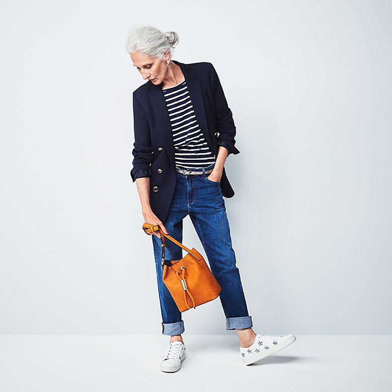 Model Sylviane wears navy blazer, striped top, relaxed jeans and white sneakers