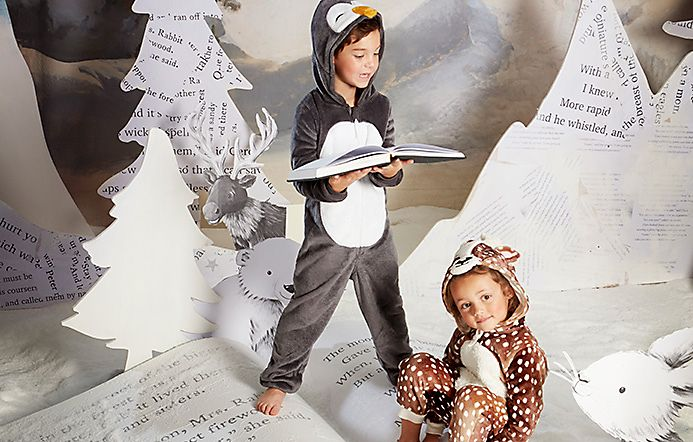 Boy and girl wear penguin and reindeer onesies
