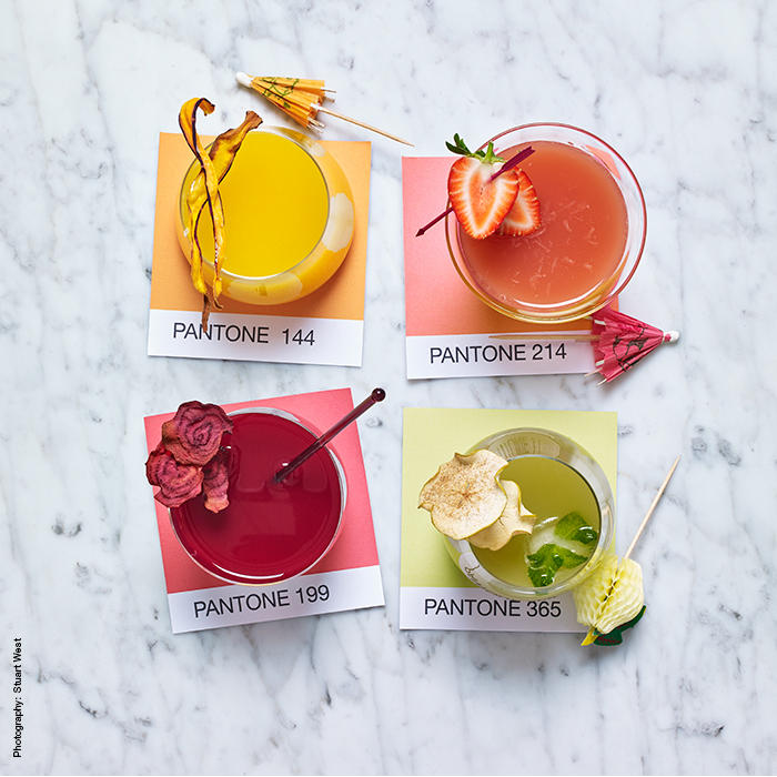 Four pastel juice cocktails with fruit garnishes on pantone colour swatches
