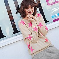 Woman wearing a beige and pink star-print jumper and grey joggers