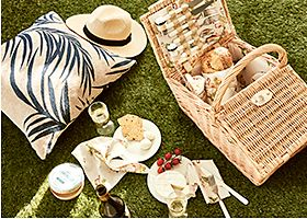 Picnic hamper and items set out on the grass