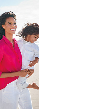 Woman and girl on a beach wearing linen clothing