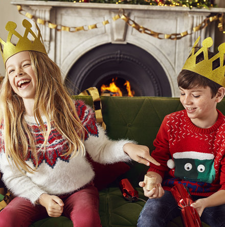 Arrangement of baubles and a boy and girl wearing Christmas jumpers pulling a cracker