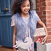 Girl wearing a sequin dress, faux-fur gilet and unicorn bag holding a Christmas gift