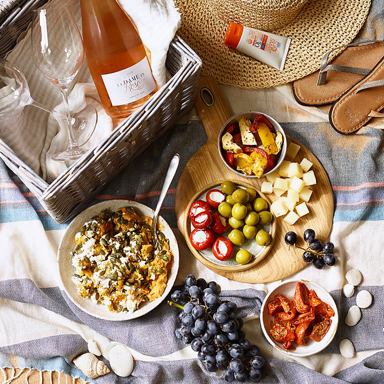 A beach picnic with rosé, dips, grapes and a picnic basket