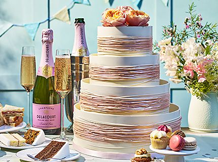 Wedding cake surrounded by slices of cake and champagne
