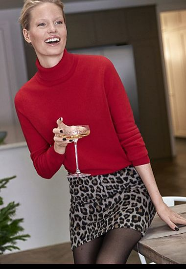 Model wears red cashmere polo neck and leopard-print skirt