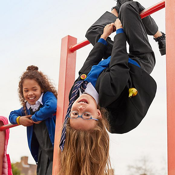 Girls in school uniform playing on a climbing frame