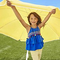 Girl stood under a yellow parasol wearing a blue embroidered top and yellow jeans