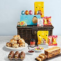 An Easter hamper with chocolate eggs, hot cross bus and cake