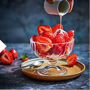 Cream being poured over a bowl of sliced strawberries