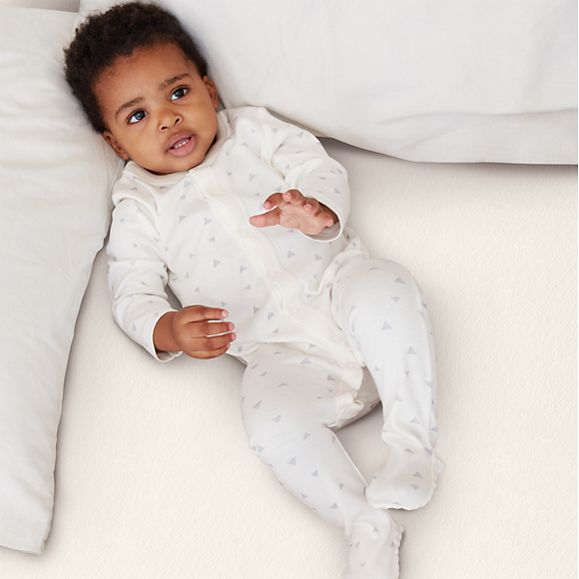 Baby wearing white M&S sleepsuit